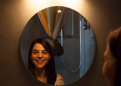 Mayte Alguacil sesion mirando al espejo sonriendo en color con filtro